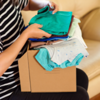 volunteer-with-donations-for-poor-people-cardboard-box-with-clothes-for-charity